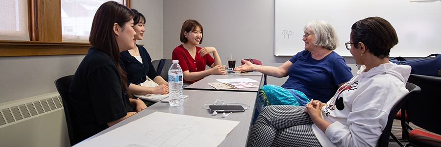 Margee Stienecker, a part-time tutor in the English as a Second Language Institute at UW-Stout, talks with international students during a recent conversation hour on campus. Stienecker said the conversations help broaden peoples' perspectives and enrich their lives.