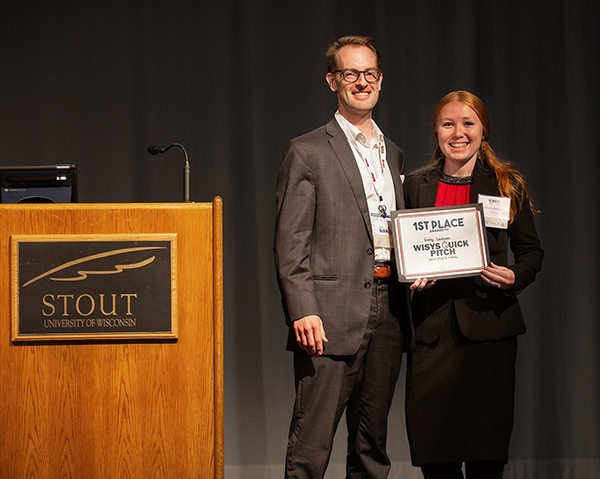 Aaron Hagar, vice president of entrepreneurship and innovation for the Wisconsin Economic Development Corporation, presents Lehmann with the first prize in the WiSys Quick Pitch state final. WEDC sponsored the event.
