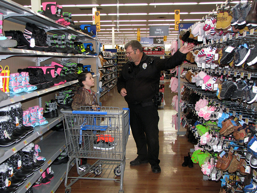 UW-Stout Police officer Corey Hein, at right, shops at Menomonie's Wal-Mart on Dec. 1 with Noah Scofield, a Menomonie fourth grader, during the Shop with a Cop program.