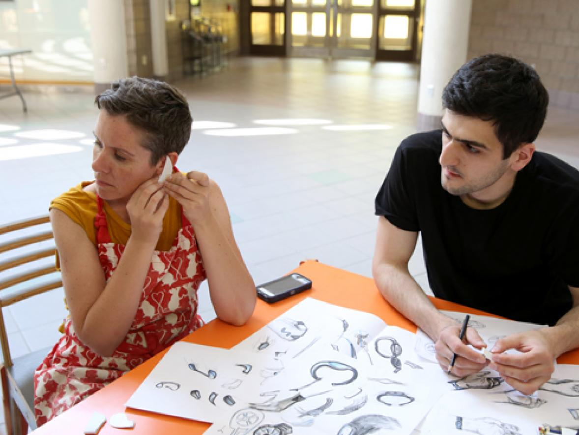 UW-Stout Associate Professor Jennifer Astwood, left, and visiting Russian scholar Azamat Tavitov try a prototype of a sensory safety device that would fit over a person's ear.