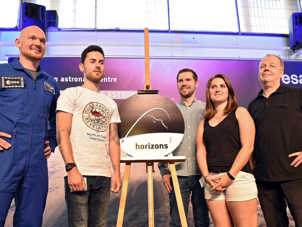 Megan Luedke takes part in a news conference to unveil the mission patch for German astronaut Alexander Gerst, left. Second from left is another student from the class, along with a class assistant and her professor, right.