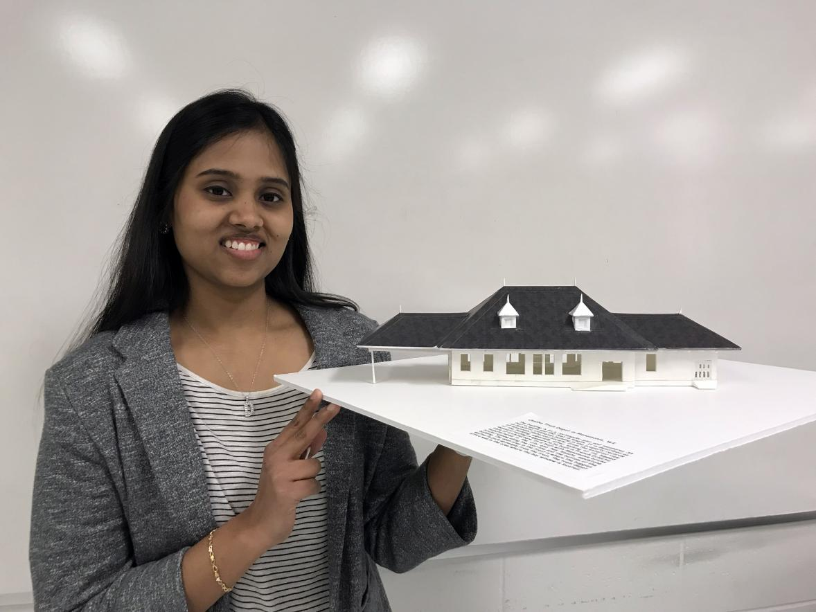 UW-Stout graduate Dharshana Gopalakrishnan holds a model of the Omaha depot. She used a 3D printer to create the model.