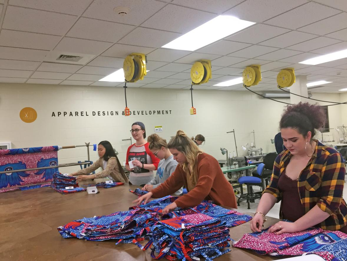 Nkao Hle Hang, at left, Sofia Van Tassel, Kennedy Gorres, Courtney Schmitt and Brynnda Foster fold skirts made by apparel design and development students as demo models for Hope Sewn.