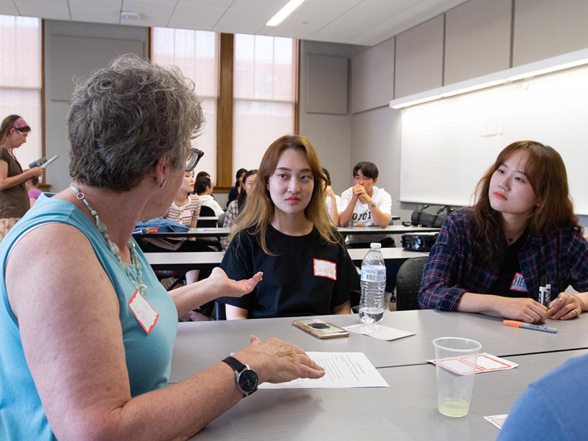 Sue Foxwell, at left, talks with South Korean students Sangha Lee and Heeju Jang during the conversations with international students.
