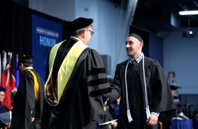 Dean Chuck Bomar congratulates Supply Chain Management graduate Andrew Reiter as he crosses the stage during Commencement for the College of Science, Technology, Engineering, Mathematics and Management.