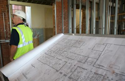 Man wearing a safety vest and hardhat stands next to renovation plans.