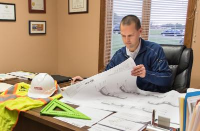 President/CEO Jim Bunkelman of Royal Construction, Inc. looks at blue prints for a construction project as he works at the office in Eau Claire, Wisconsin.